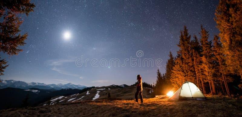 男性游人充分有休息在他的阵营在森林附近在晚上在美丽的夜空下星和月亮 库存照片