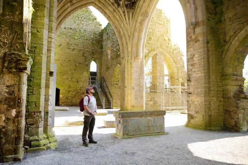 男性游人在Jerpoint修道院,一个被破坏的Cistercian修道院里,位于在Thomastown附近,基尔肯尼郡,爱尔兰 库存图片