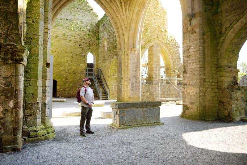 男性游人在Jerpoint修道院,一个被破坏的Cistercian修道院里,位于在Thomastown附近,基尔肯尼郡,爱尔兰 免版税库存照片