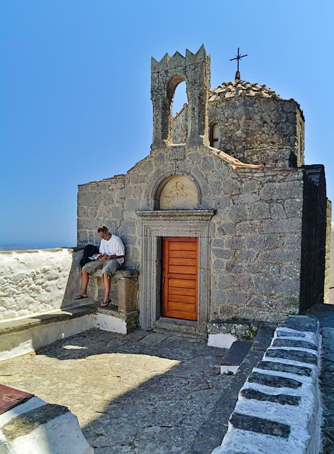 男性游人读在教堂前面的一本书 库存照片