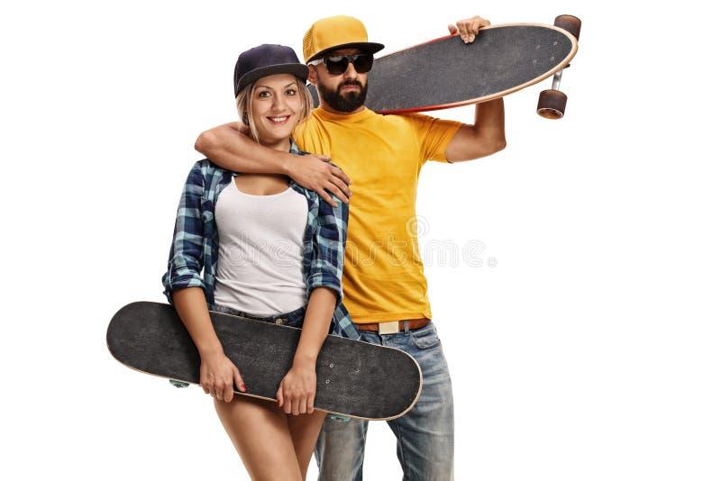 男性溜冰者举行longboard的和举行skateboa的女性溜冰者 免版税图库摄影