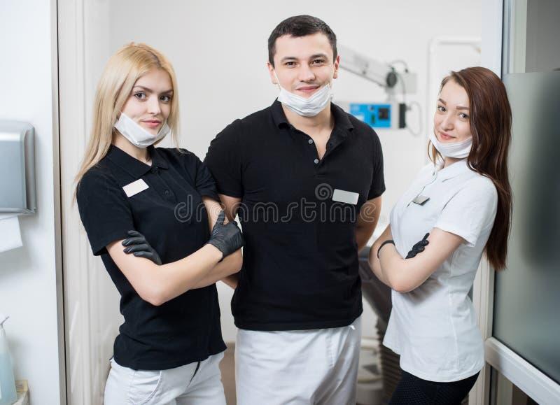 男性牙医和两个女性助理画象在牙齿办公室 免版税图库摄影