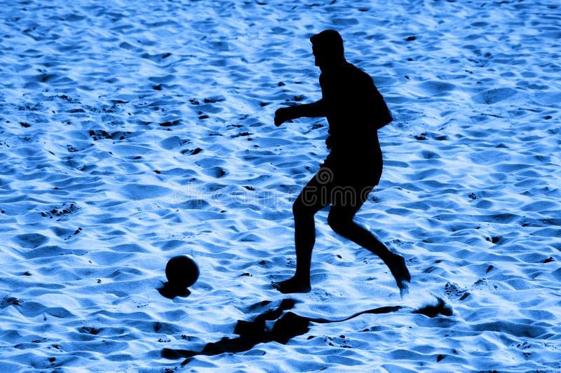 男性球员的现出轮廓的海滩足球行动沙子的 蓝色滤色器 图库摄影