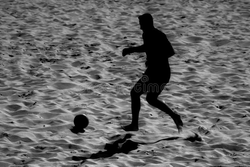 男性球员的现出轮廓的海滩足球行动沙子的 免版税库存照片