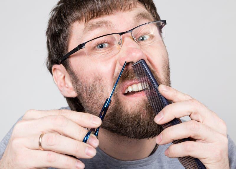 男性理发师剪他在鼻子的自己的头发,看象镜子的照相机 时髦的专业美发师 库存图片