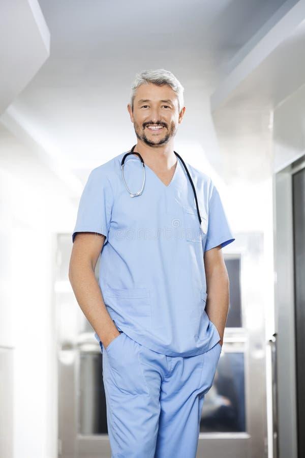 男性生理治疗师用在站立在修复Cen中的口袋的手 免版税库存照片