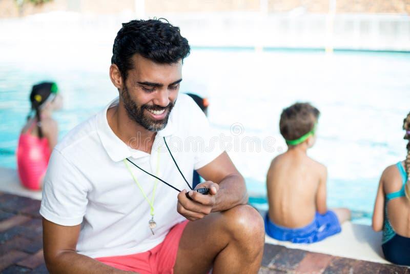 男性由孩子的辅导员观看的秒表游泳池边的 免版税库存照片