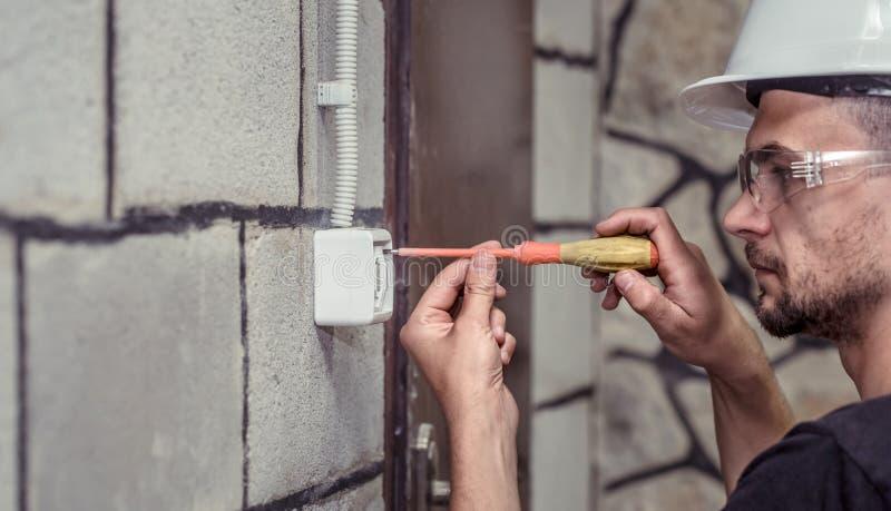 男性电工技术员,用工具连接设备 免版税库存照片