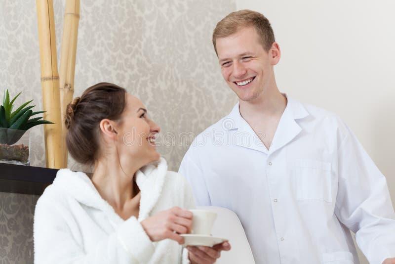 男性男按摩师谈话与他的女性患者 免版税图库摄影