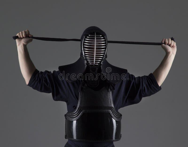 男性画象在传统kendo装甲的投入他的盔甲和为战斗做准备 免版税库存图片