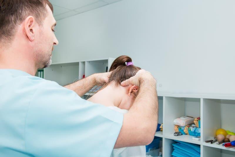 男性神经学家医生审查女性耐心脊柱的颈椎在诊所的 神经学物理exami 免版税库存照片