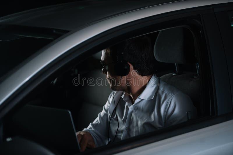 男性私家侦探侧视图做与膝上型计算机的耳机的监视 免版税库存照片