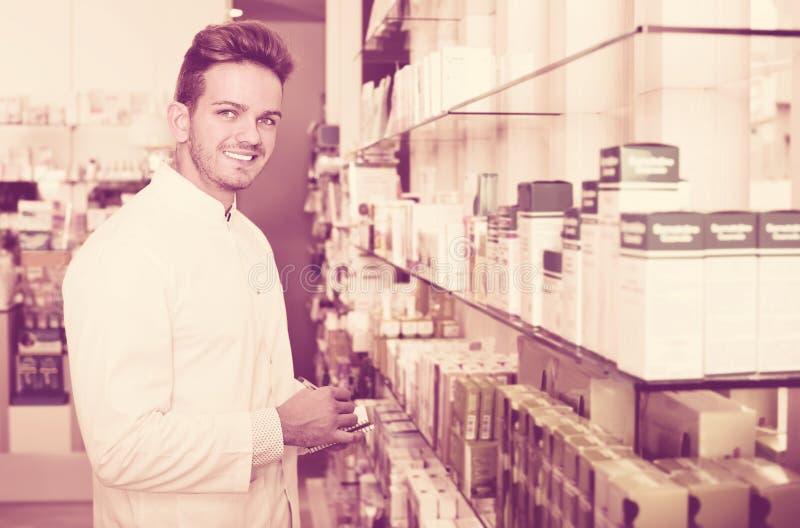 男性站立在药店的药剂师佩带的白色外套 库存照片