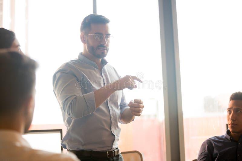 男性组长谈话谈论想法与不同的同事 免版税库存图片
