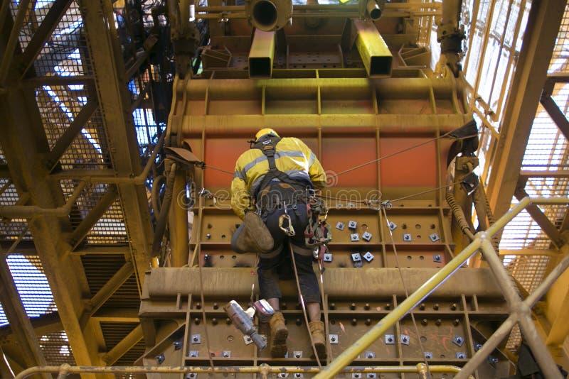 男性绳索通入产业工作者佩带的安全带,秋天保护盔甲垂悬的工作在Y吊绳索位置 免版税库存照片