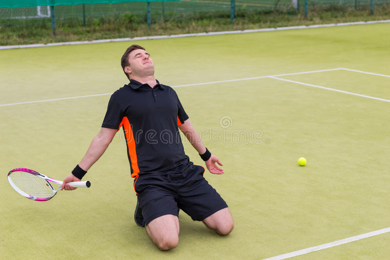 男性网球员坐他的膝盖由于损失我 免版税库存图片