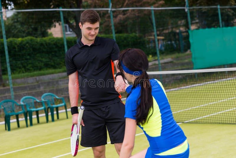 男性网球员帮助他的女性伙伴站起来 库存照片