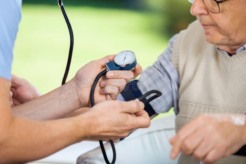 男性老人看守者测量的血压  免版税图库摄影