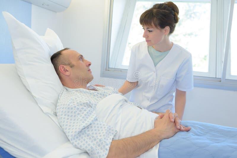 男性耐心谈话与女性护士在急诊室 库存图片