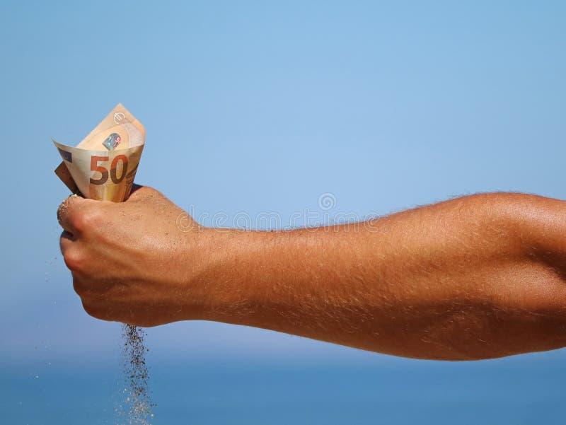 男性胳膊在蓝色海背景,假日费用的概念拿着五十欧元钞票并且通过让沙子细流 免版税库存照片