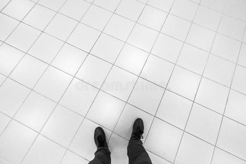 男性脚在与白色瓦片的办公室地板上站立 免版税图库摄影