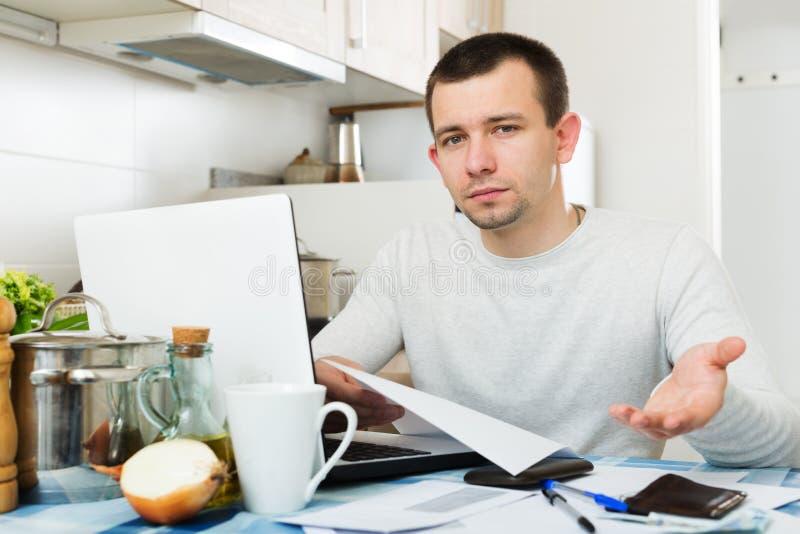 男性自由职业者读书在膝上型计算机附近裱糊 库存照片