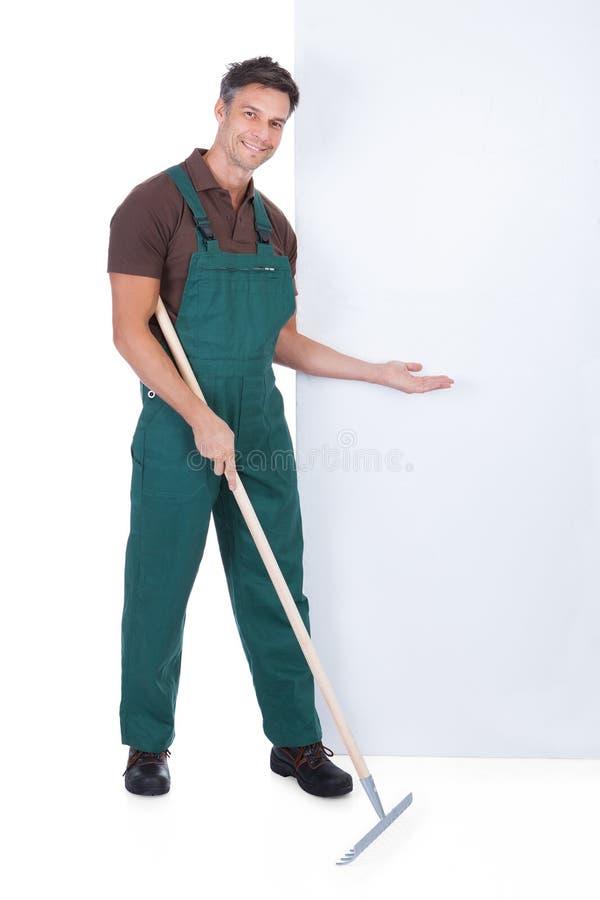 男性花匠与干草叉一起使用 免版税库存照片