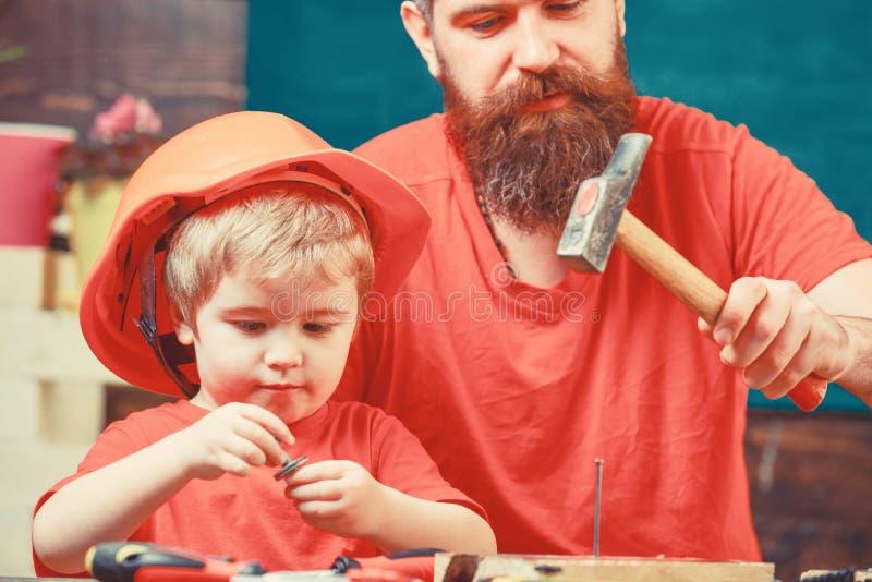 男性责任概念 生,做父母与教小儿子的胡子使用短钉和锤子 男孩,繁忙的孩子  库存照片