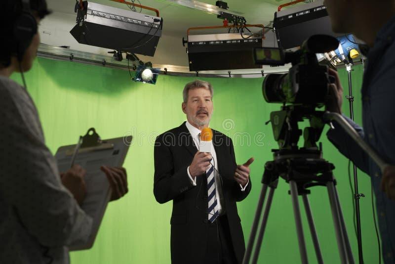 男性赠送者在有乘员组的电视演播室在前景 库存照片