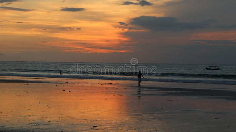 男性走在海滩岸和使用在水中的孩子在日落 库存图片