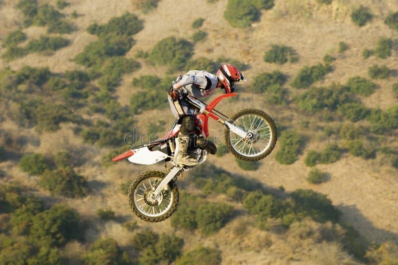 男性车手飞行通过与摩托车的空气 库存照片