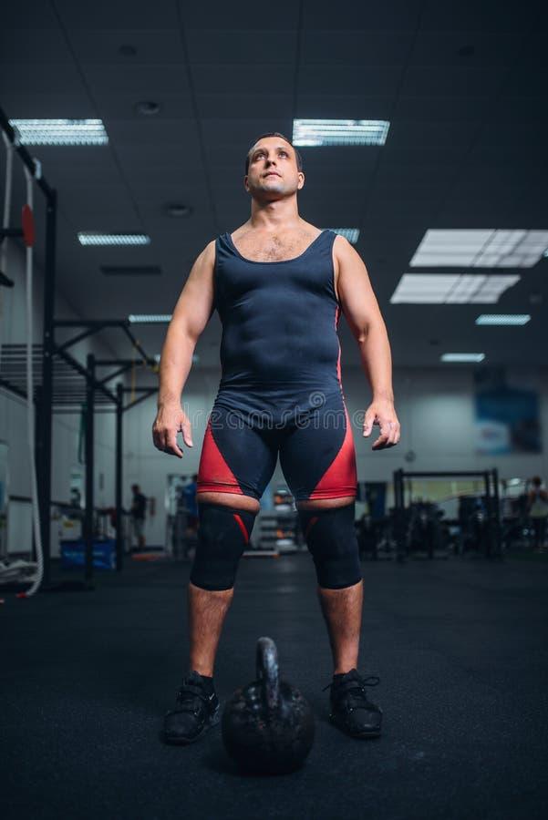 男性运动员为与kettlebell的锻炼做准备 免版税库存图片