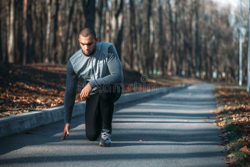 男性运动员准备跑,训练室外 免版税图库摄影