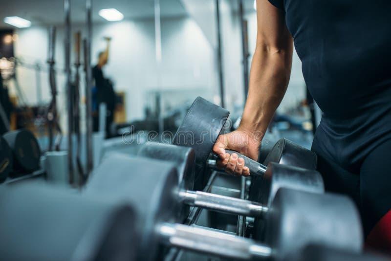 男性运动员在手中采取重的哑铃 库存图片