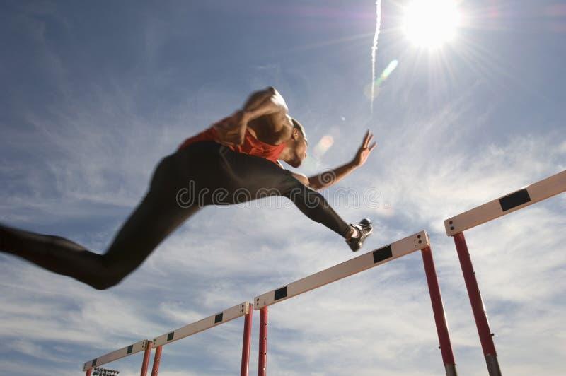 男性运动员跳跃的障碍 库存图片
