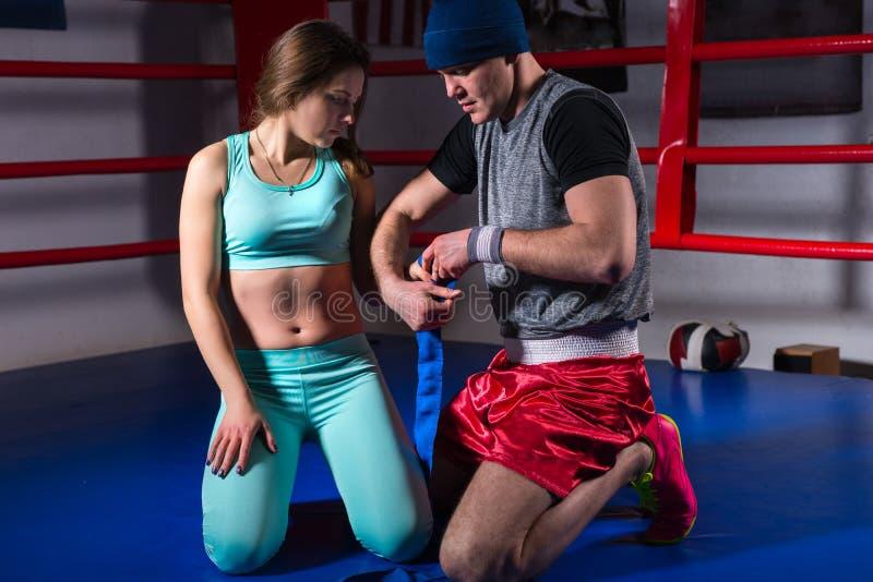男性运动的拳击手绷带为年轻女性做准备 免版税库存照片