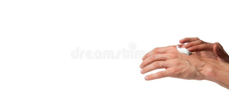 男性运转的手在白色背景上把被隔绝的软的皮肤的,秀丽概念润湿奶油放 免版税图库摄影