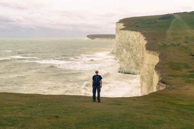 男性远足者佩带的背包从后面敬佩七个姐妹白色峭壁  免版税库存图片