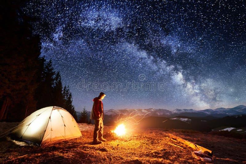 男性远足者充分有休息在他的阵营在森林附近在晚上在美丽的夜空下星和银河 图库摄影