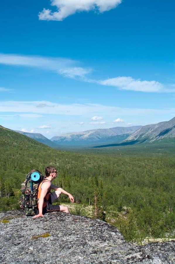 男性远足者开会和放松在山 免版税库存图片