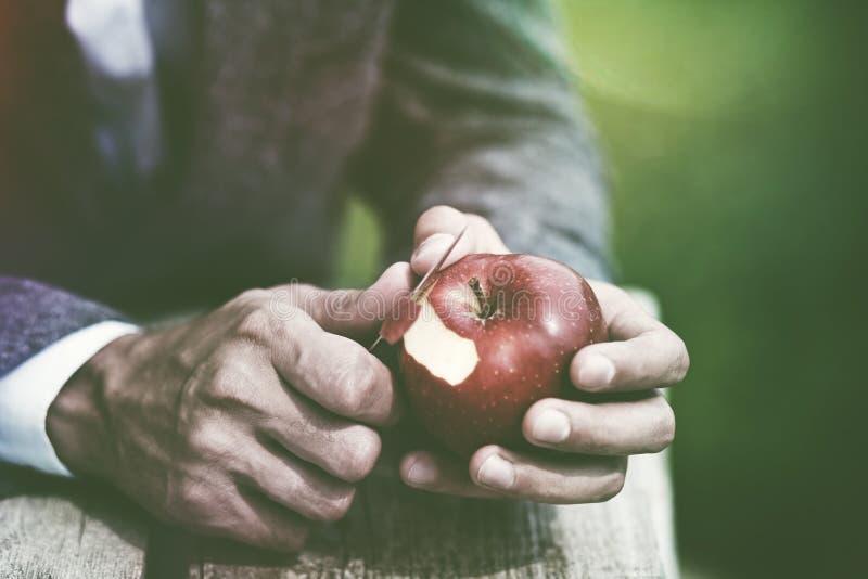 男性递与刀子的削皮苹果 免版税库存图片