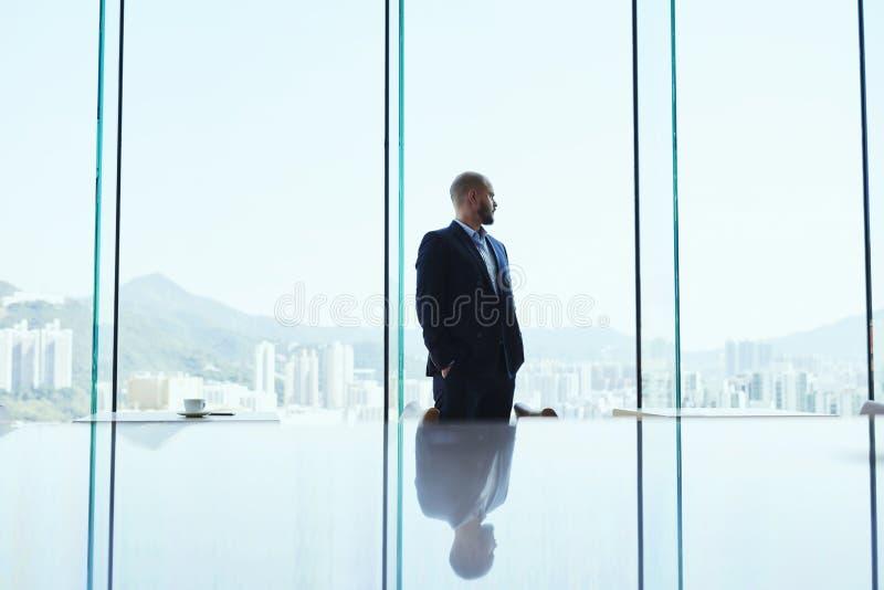 男性银行家在内部现代的办公室在商业区的窗口里站立并且观看 图库摄影
