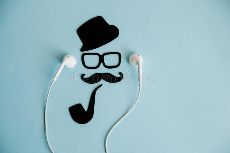 男性面孔和髭和辅助部件绅士图象听的音乐与耳机 免版税库存照片