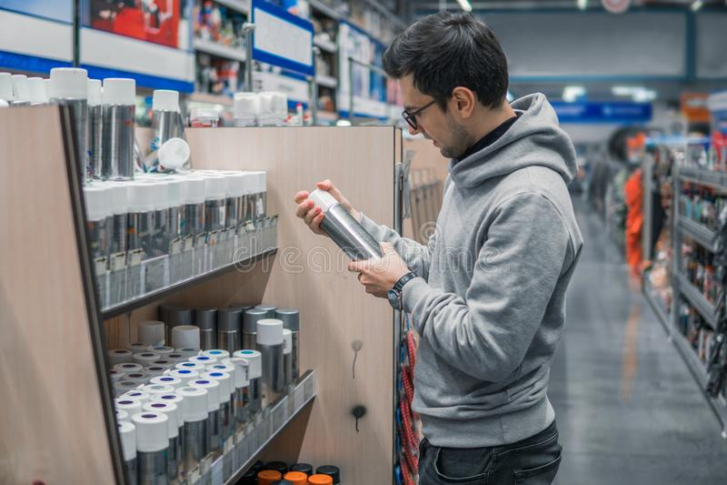 男性顾客买的喷漆在超级市场能 免版税库存图片