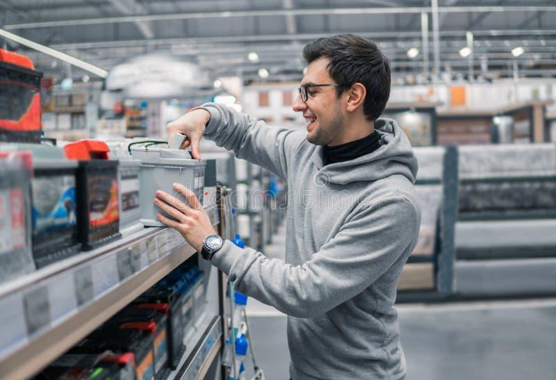 男性顾客买的汽车电池n汽车超级市场 免版税库存照片