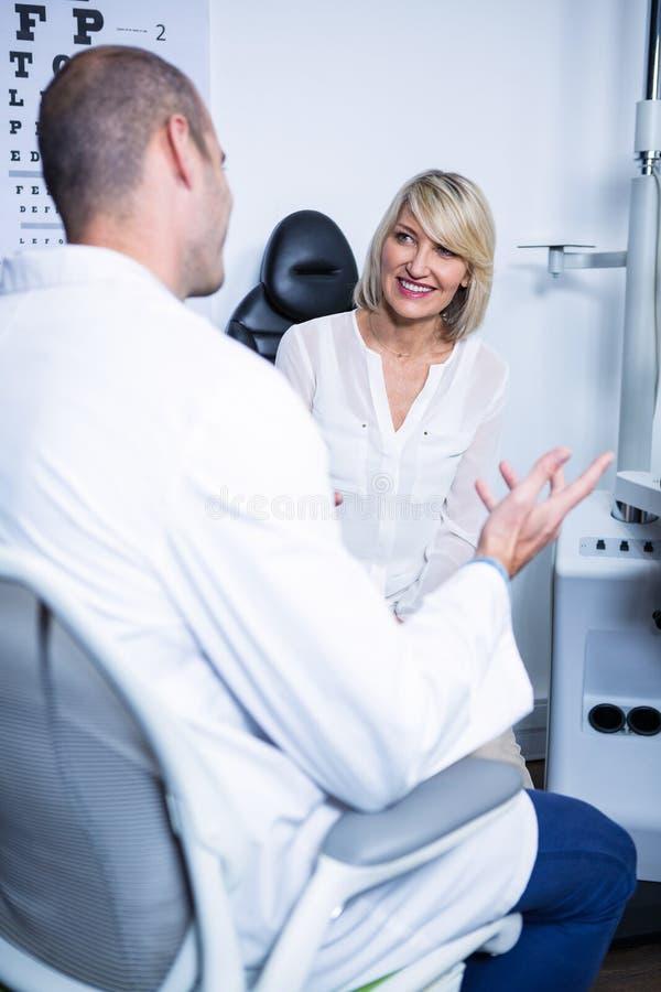 男性验光师谈话与女性患者 免版税图库摄影