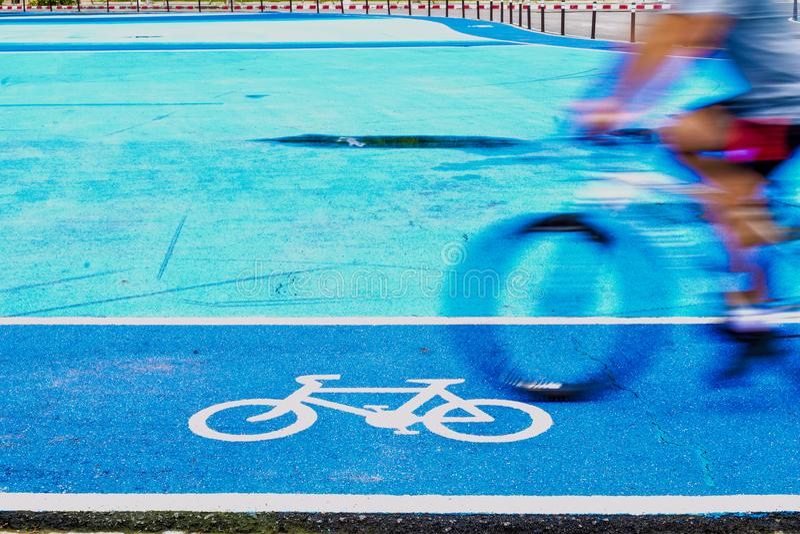 男性骑自行车者在自行车标志车道骑自行车  免版税图库摄影