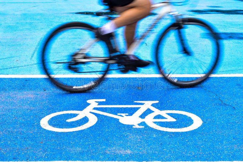 男性骑自行车者在自行车标志车道骑自行车  免版税库存照片