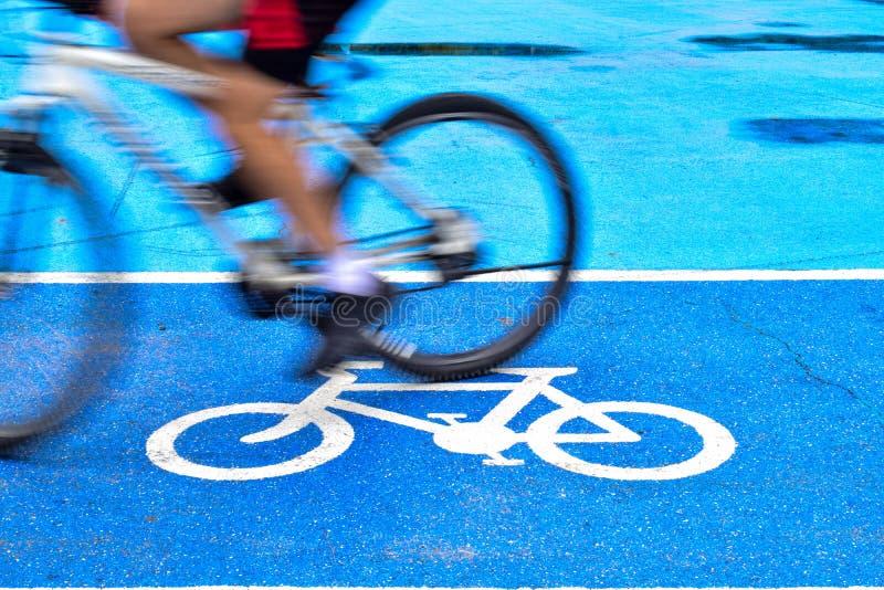 男性骑自行车者在自行车标志车道骑自行车  库存图片
