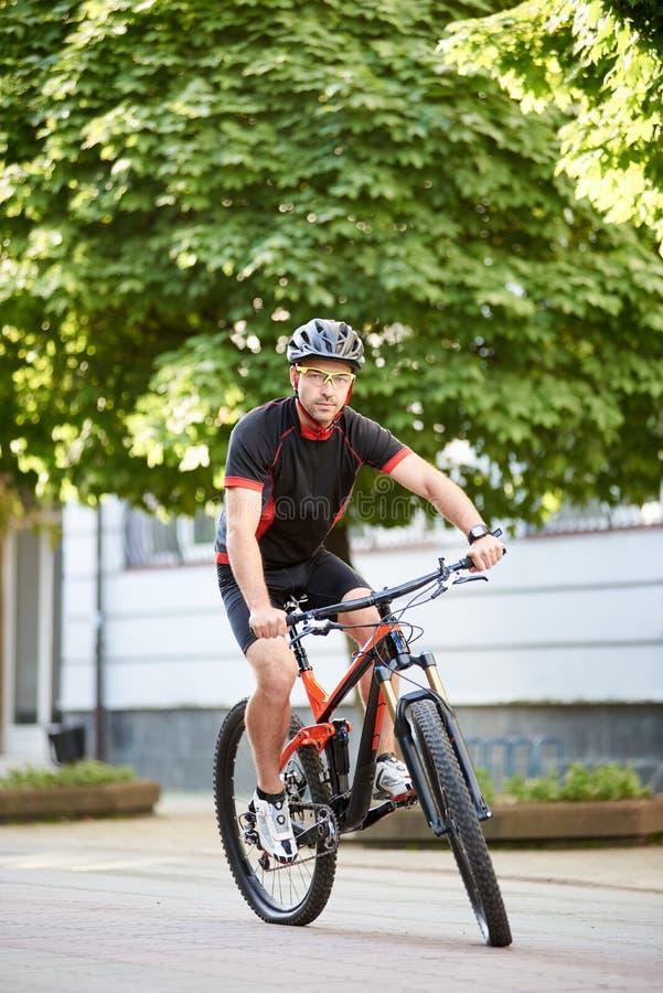 男性骑自行车者训练在市中心 库存照片